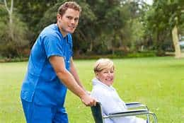 Male caregiver pushing patient in wheelchair|How To Care With Tender Loving Care