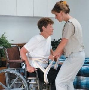 Nurse helping patient in a transfer sling and gait belt|How Caregivers Use Transfer Aids