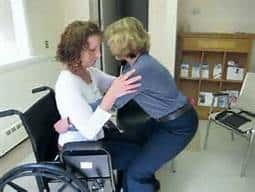 Aide putting patient in wheelchair|How Caregivers Use Transfer Aids