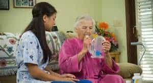 Caregiver helping with spirometer|Solutions for Better Breathing in Older Adults
