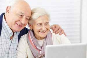 Husband and wife looking on computer 12 Useful Gadgets For Your Senior Parents