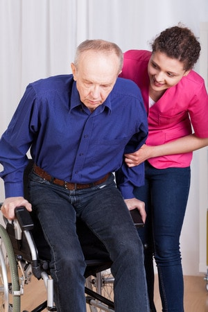 Man in wheelchair with nurse|How to care for your loved one with Amyotrophic Lateral sclerosis (ALS)