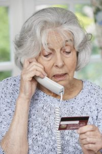 Senior woman giving credit card information|How to handle when a senior parent is being scammed