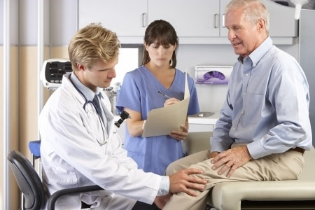 Doctor and nurse examining mans knee|How