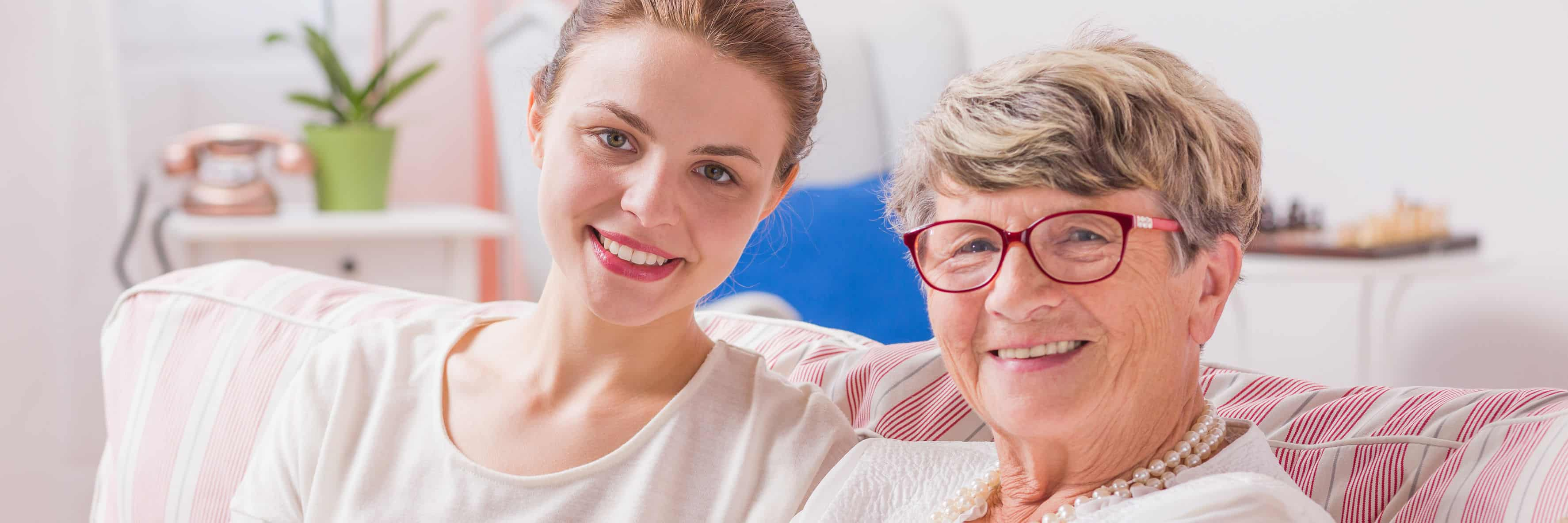 65560848 - happy daughter and her senior mother sitting together on a sofa, panorama